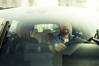 Looking inside a Hyundai through the windshield, a family in the car is looking happy.